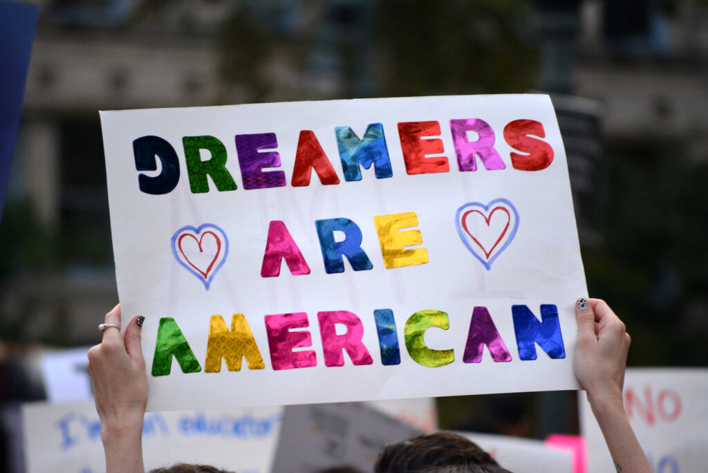 A sign that says Dreamers are American in colorful letters