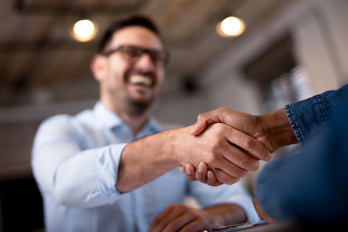 immigration lawyer shaking hands with a client and smiling